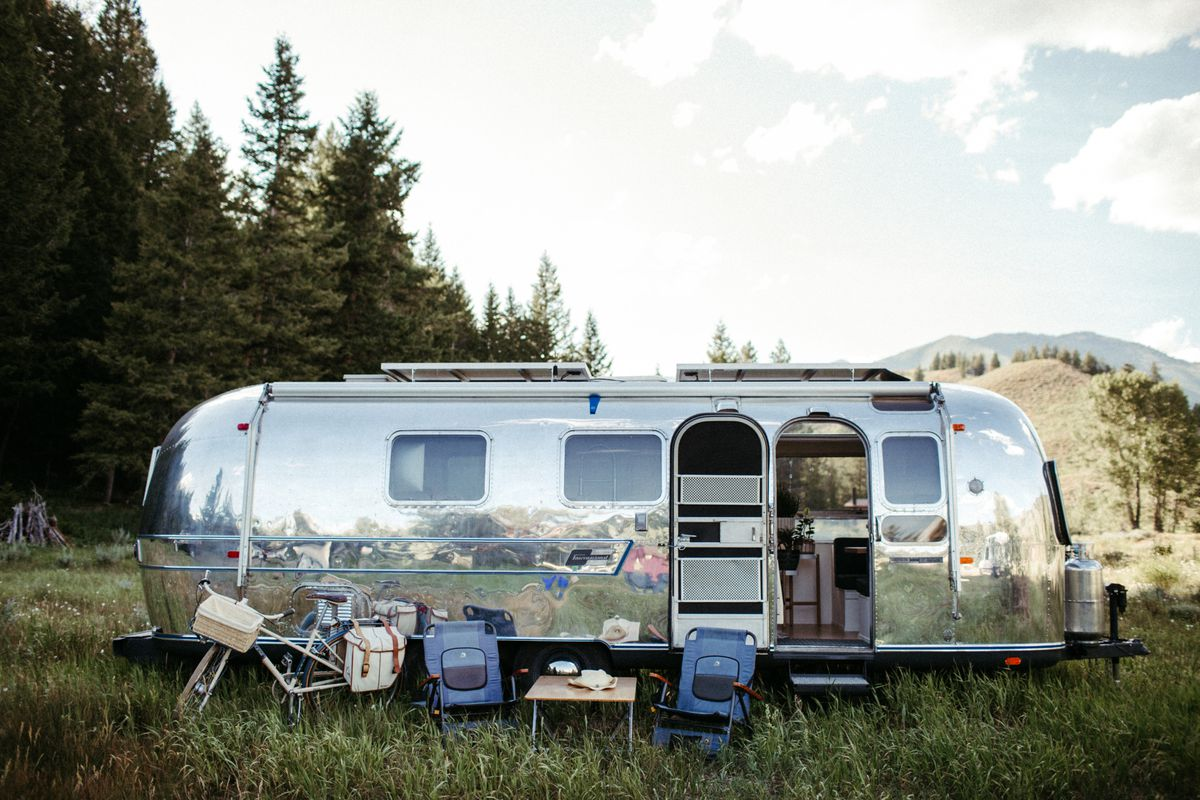A shiny silver Airstream camper trailer sits in a green field with trees around.