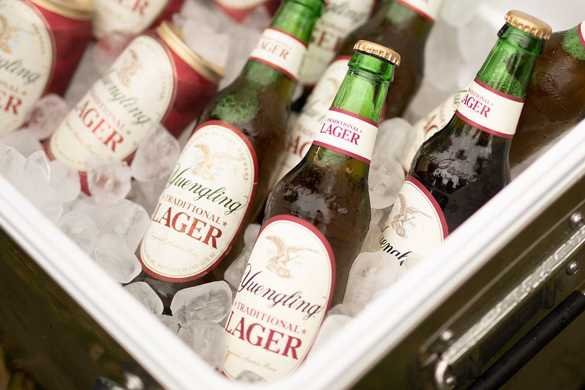 an ice chest full of bottles and cans of yuengling beer and ice