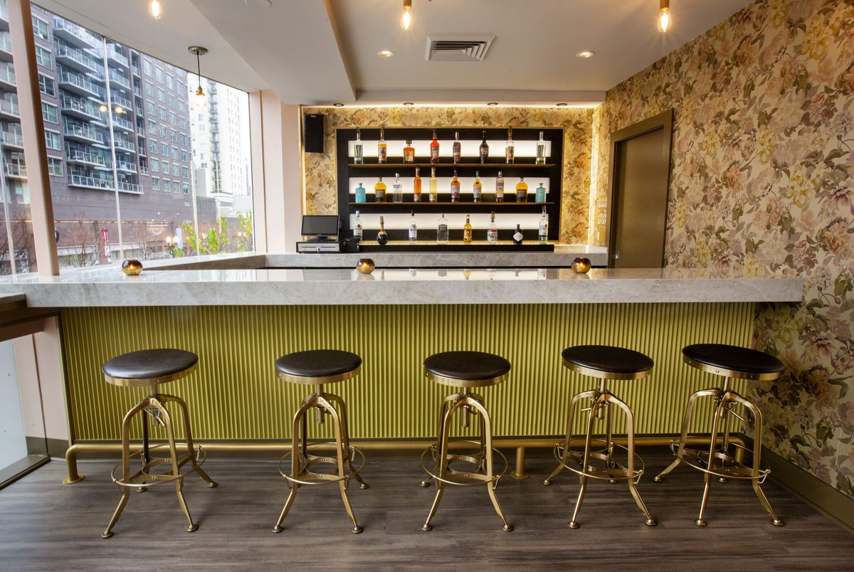 A smallish marble-topped bar with green underneath and five bar stools.