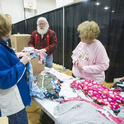 Charlotte Collard and Susan Hawkins talk with Merlin Taylor as they get clothing ready the opening of the 19th annual Candy Cane Corner holiday store at the old Granite High School pool building in South Salt Lake on Monday, Nov. 30, 2015.
