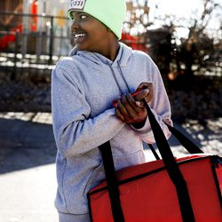 Glendale Middle School student Dede Gass helps deliver lunches to Glendale students and their families who reside at Seasons at Pebble Creek in Salt Lake City on Tuesday, Dec. 29, 2020. Publik Kitchen cooked almost 300 meals over three days for Glendale Middle School students and their families through the Nourish to Flourish initiative. The initiative, which started in response to the COVID-19 pandemic, is a partnership between restaurants, service organizations and community funders to provide meals to those in need.