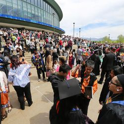 Graduates and their families gather outside the Maverik Center in West Valley City following Salt Lake Community College's commencement ceremony on Friday, May 6, 2016.