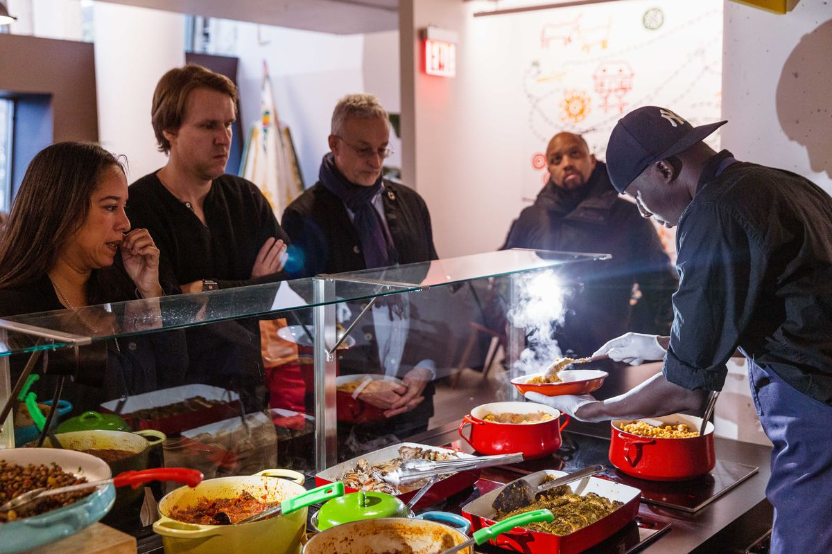 Patrons queue up as a Teranga staffer in a Yankees uses a spoon to plate a steamy bowl of couscous