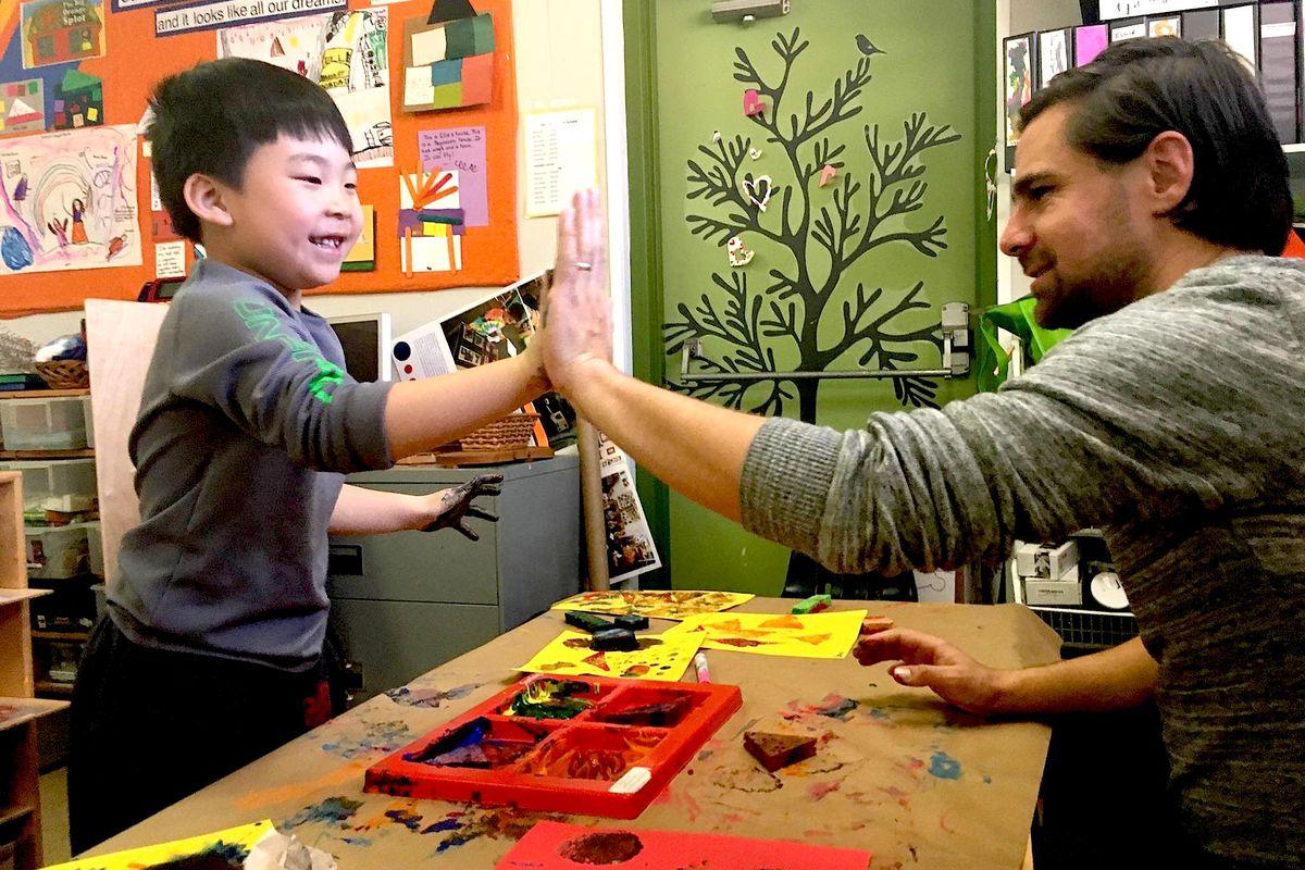 Graham Carson, a teacher at Denver Cooperative Preschool, finger paints with a student.