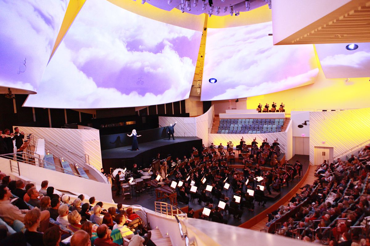 The interior of New World Center in Miami. The ceiling has various large panels which have video projections of clouds on them. There is a person singing on the stage and an orchestra performing in the orchestra pit.