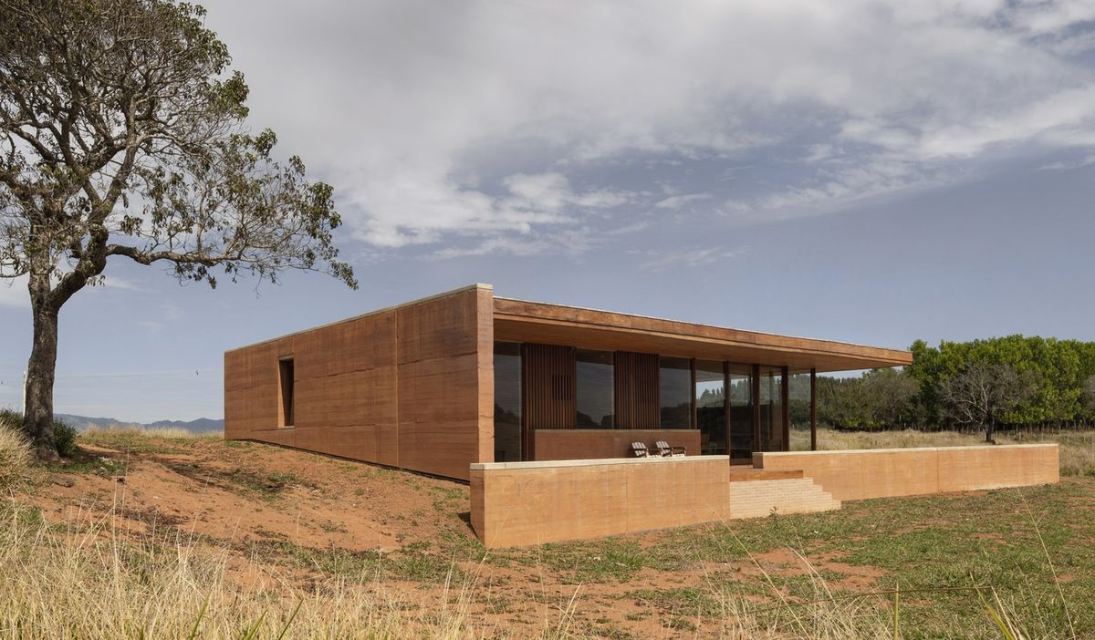 Exterior shot of house built from rammed earth with a covered porch.
