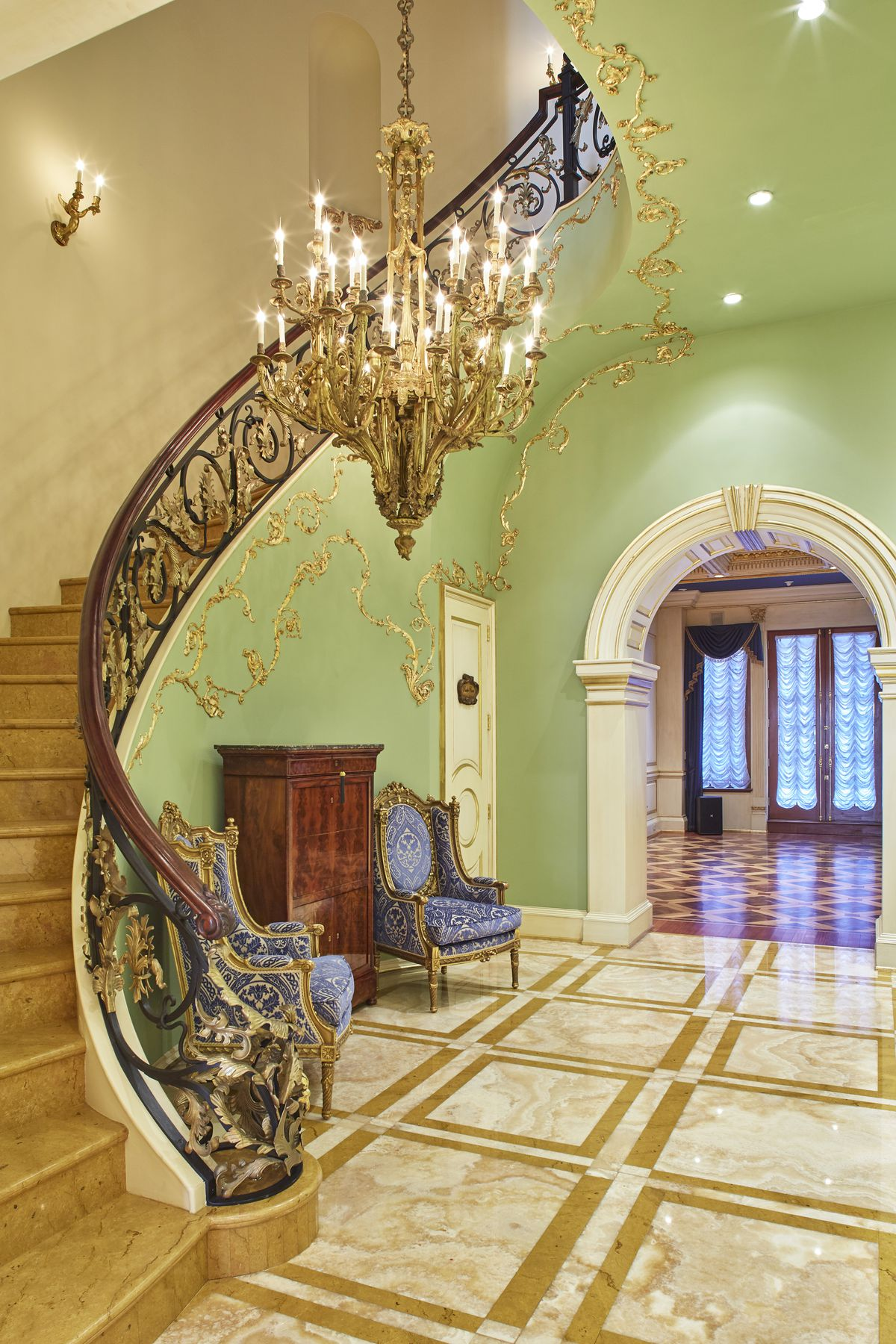 A marble staircase with elegant railings, a large chandelier next to it.
