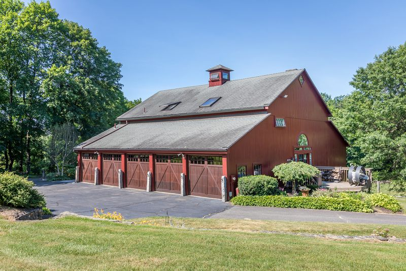 An exterior view of the red barn home's attached five car garage with driveway and green trees.