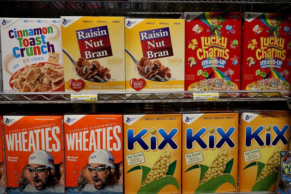 Boxes of breakfast cereal on a shelf, including Kix, Wheaties, Lucjy Charm, Cinnamon Toast Crunch, and Raisin Nut Bran.