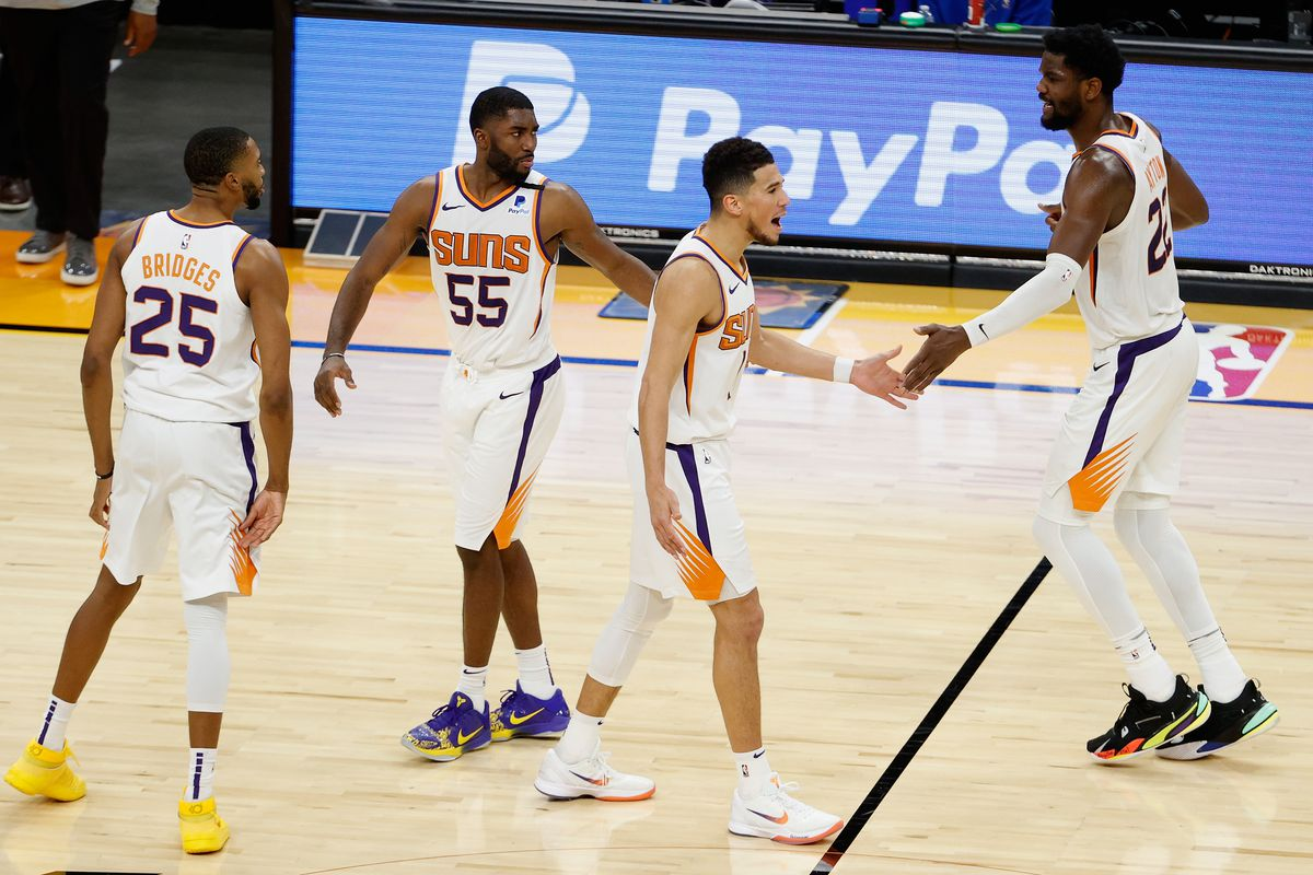 Devin Booker #1 of the Phoenix Suns celebrates with Mikal Bridges #25, E'Twaun Moore #55 and Deandre Ayton #22 after scoring against the Cleveland Cavaliers during the second half of the NBA game at Phoenix Suns Arena on February 08, 2021 in Phoenix, Arizona. The Suns defeated the Cavaliers 119-113.