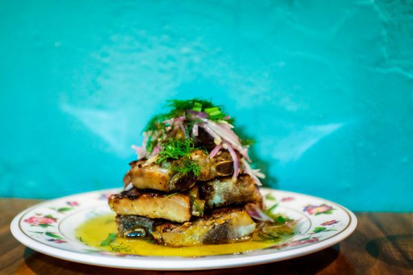 A pile of colorfully-garnished pork ribs on a china plate with a teal wall background at Little Serow