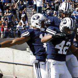 Brigham Young Cougars wide receiver Ross Apo, left, Brigham Young Cougars running back Michael Alisa and Brigham Young Cougars wide receiver Cody Hoffman celebrate a touchdown as Brigham Young University faces Idaho State in NCAA football in Provo, Saturday, Oct. 22, 2011.