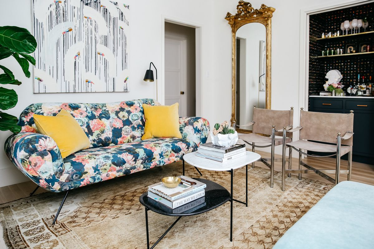 LIving room with white walls, eclectic furniture, floral couch