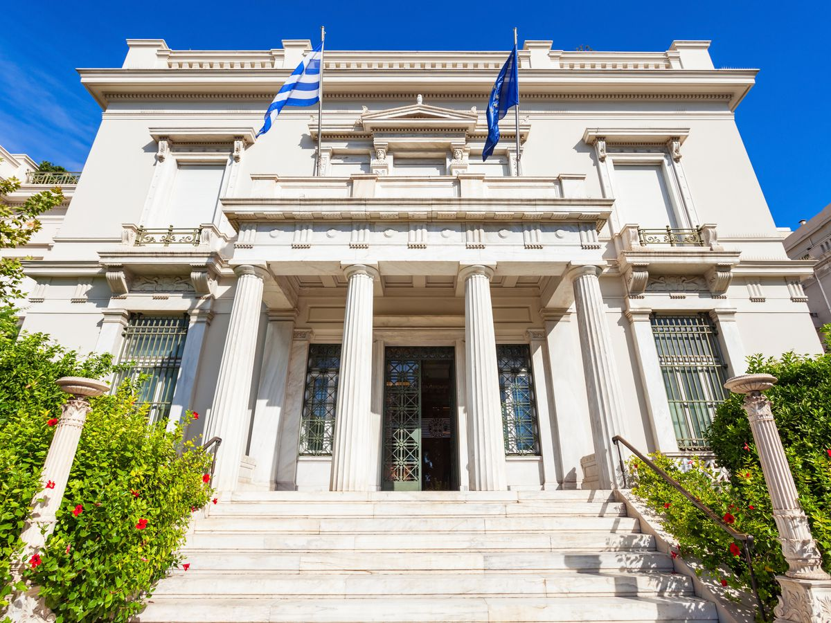 The exterior of the Benaki Museum in Athens. The facade is white with columns and a grand staircase.