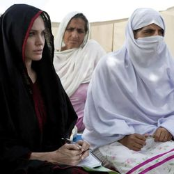 In this photo provided by the United Nations High Commission for Refugees, Angelina Jolie, left, the goodwill ambassador of UNHCR, sits with Pakistani flood-affected women during her visit to a camp for people displaced by heavy floods in Nowshera, Pakistan, Tuesday, Sept. 7, 2010.