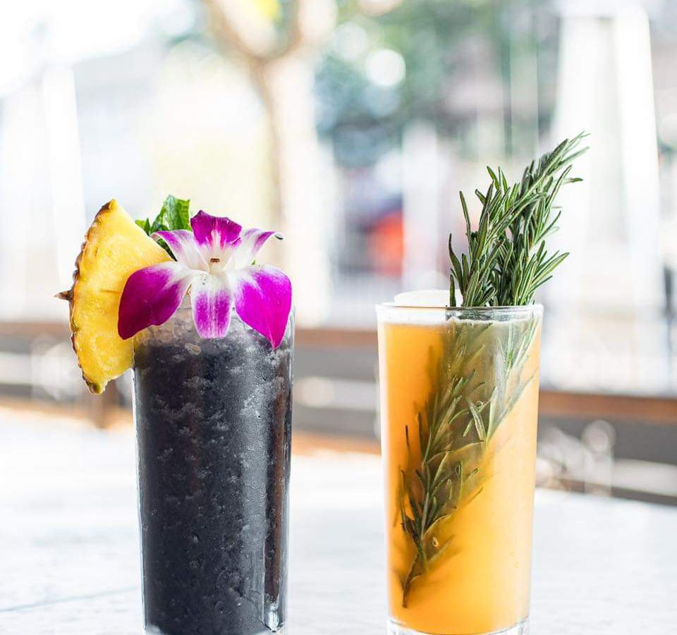 A black cocktail garnished with an orchid and pineapple next to an orange cocktail garnished with rosemary.