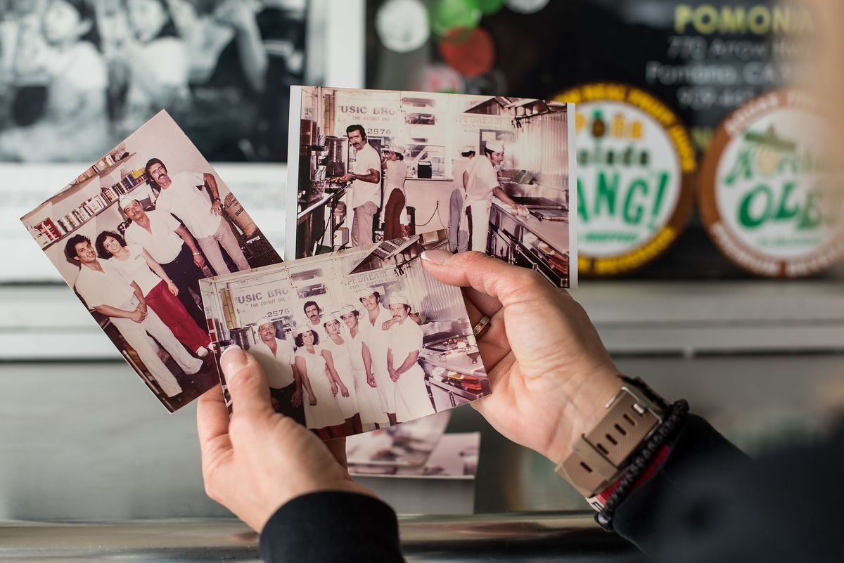 Hands hold old photographs of family in front of a restaurant.