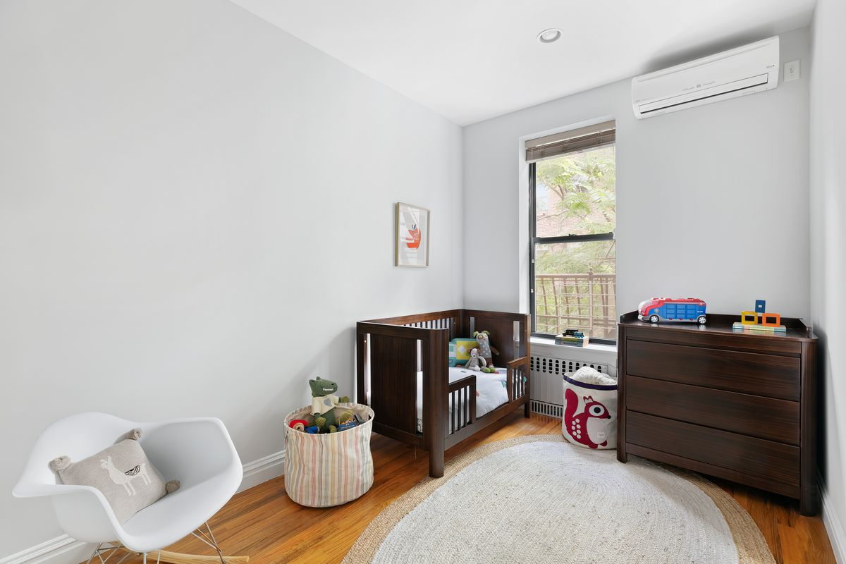 A bedroom with a window overlooking trees. There's also a brown crib and changing table.