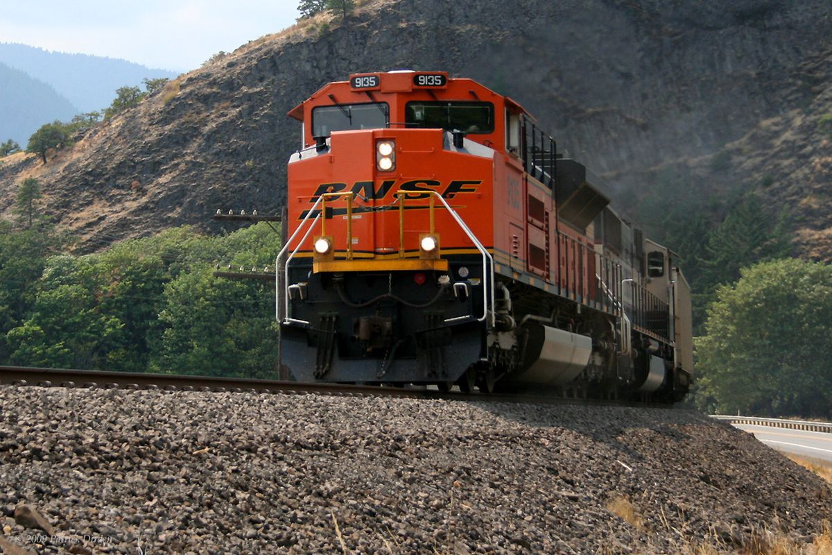 BNSF 9135 guides an empty coal train east to Wyoming, for a fresh load of coal. The train is passing Tunnel Lake, WA.