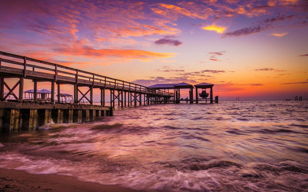 In the foreground is an ocean. There is a pier that stretches out into the distance. It is sunset and the sky is purple, orange, and blue.