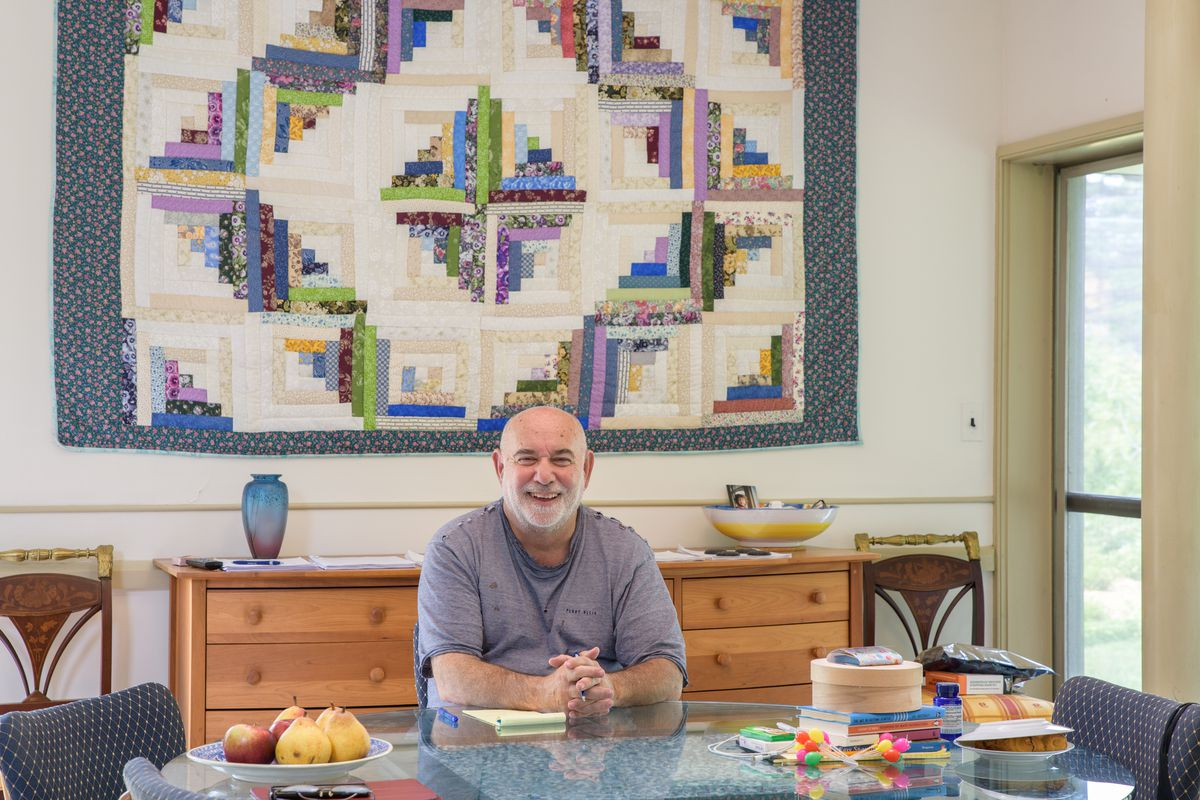 David Lockhard, the current owner of the Vanna Venturi house, sits at the dining room table smiling at the camera. On the table is a bowl of fruit, various toys, and kitchen items. Behind him is a patchwork quilt hanging on the wall above a wooden dresser