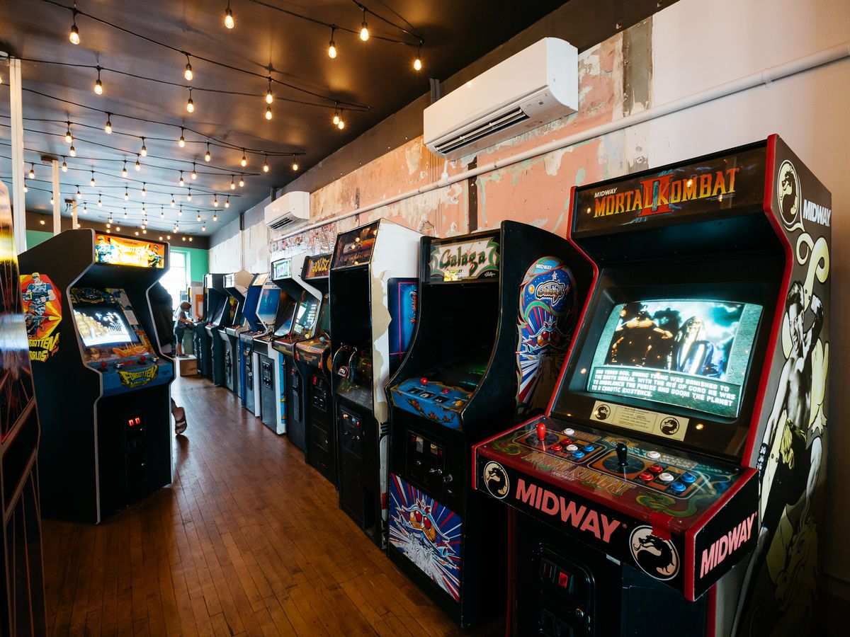 A bunch of retro game consoles in a row inside Pop + Offworld Arcade.