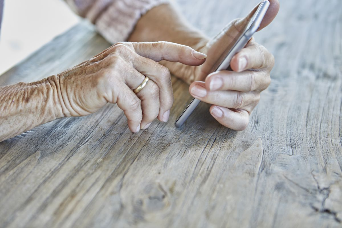 An older person's hands holding a cellphone.