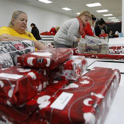 Mary Salazar, left, of Grantsville, wraps presents for children at the 13th annual Giving Tree program at Valley Fair Mall in West Valley City on Tuesday, Dec. 15, 2015. The program provides Christmas presents to 170 children from 61 low-income families in the city.