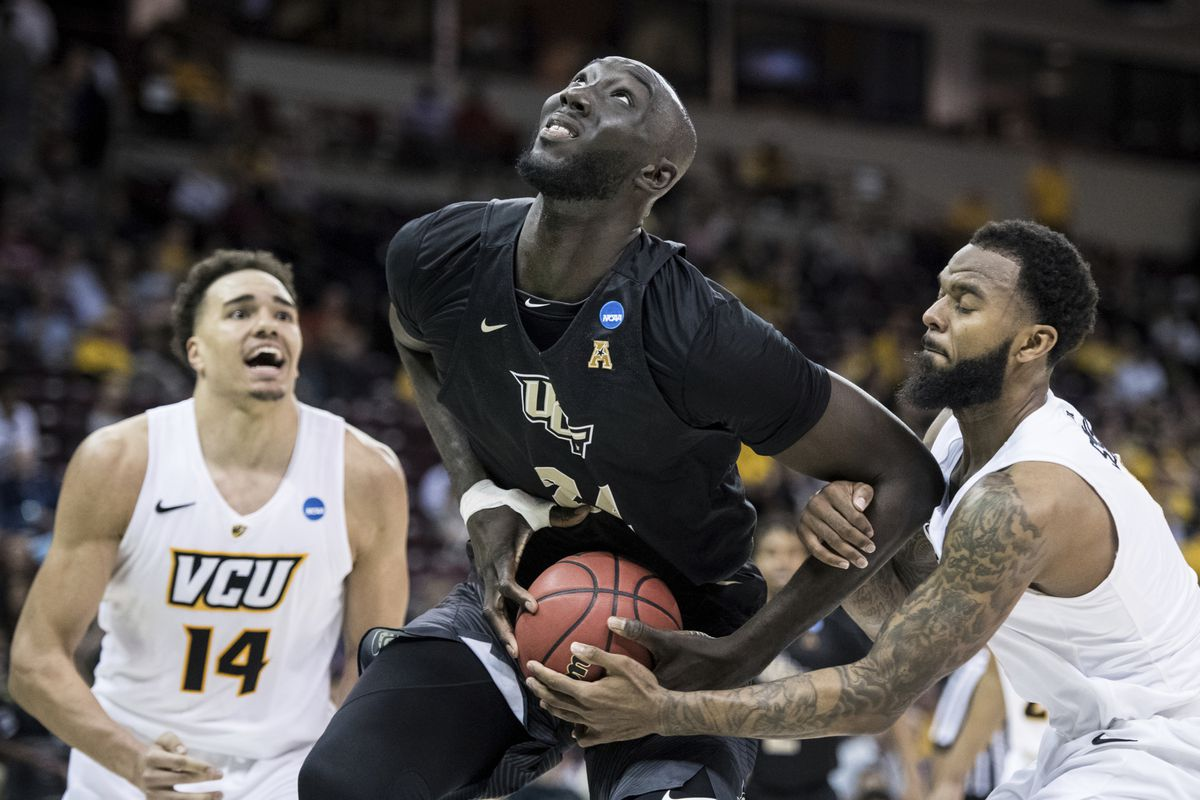 Central Florida center Tacko Fall (24) is fouled by VCU guard Mike'L Simms, right, during the second half of a first-round game in the NCAA men's college basketball tournament in Columbia, S.C.