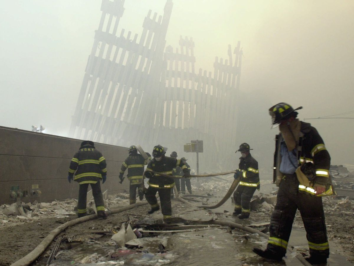 In this Tuesday, Sept. 11, 2001 file photo, with the skeleton of the World Trade Center twin towers in the background, New York City firefighters work amid debris on Cortlandt St. after the terrorist attacks.