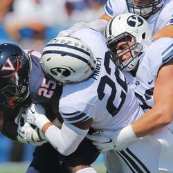 Virginia running back Kevin Parks (25) is brought down by Brigham Young linebacker Manoa Pikula (22) and others s BYU and Virginia to play Saturday, Sept. 20, 2014, at LaVell Edwards Stadium in Provo.