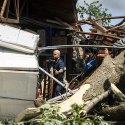 A resident works to clean out a home on Evergreen Lane near Chestnut Avenue in Woodridge after a tornado ripped through the western suburbs overnight, Monday morning, June 21, 2021.