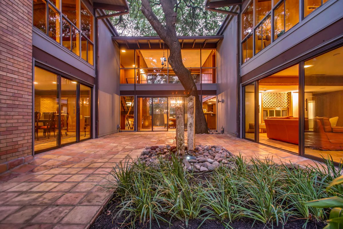 Two-story midcentury modern house courtyard with glass walls on three sides