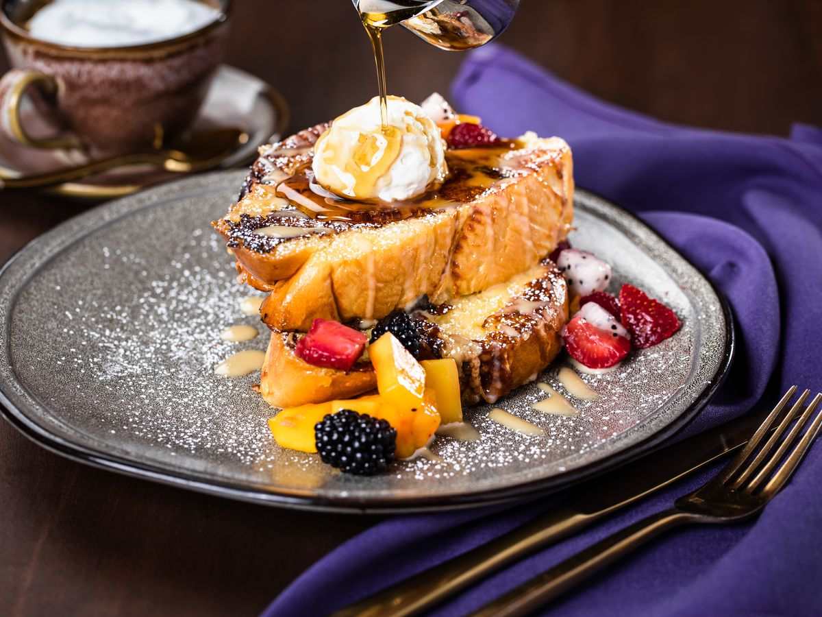 A plate of French toast with fruit