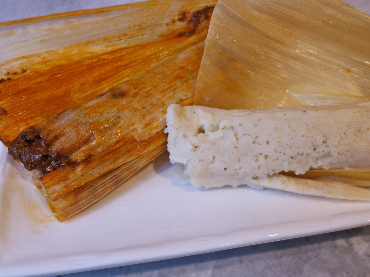 A pair of tamales, one still wrapped in corn husks.