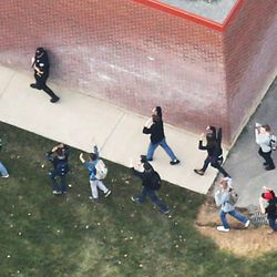 Pleasant Grove High School students are escorted into a gym that is not attached to the main high school building during a lockdown on Thursday, Dec. 3, 2015, in Pleasant Grove. A report of a man with a gun in the building turned out to be false.