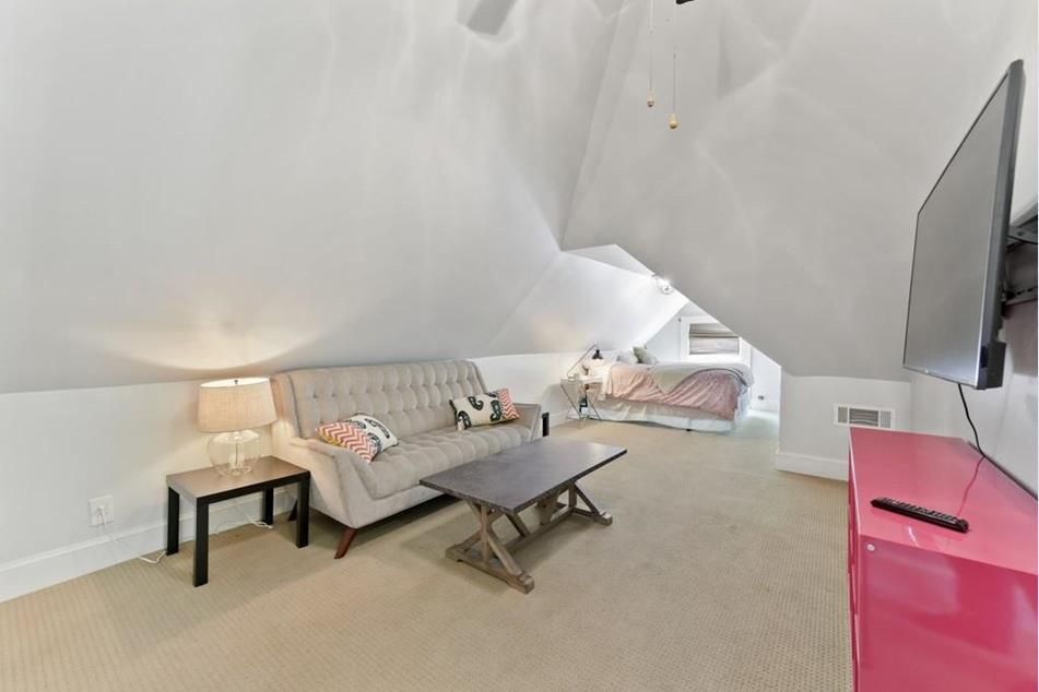 A white attic space with a  bed at the back.