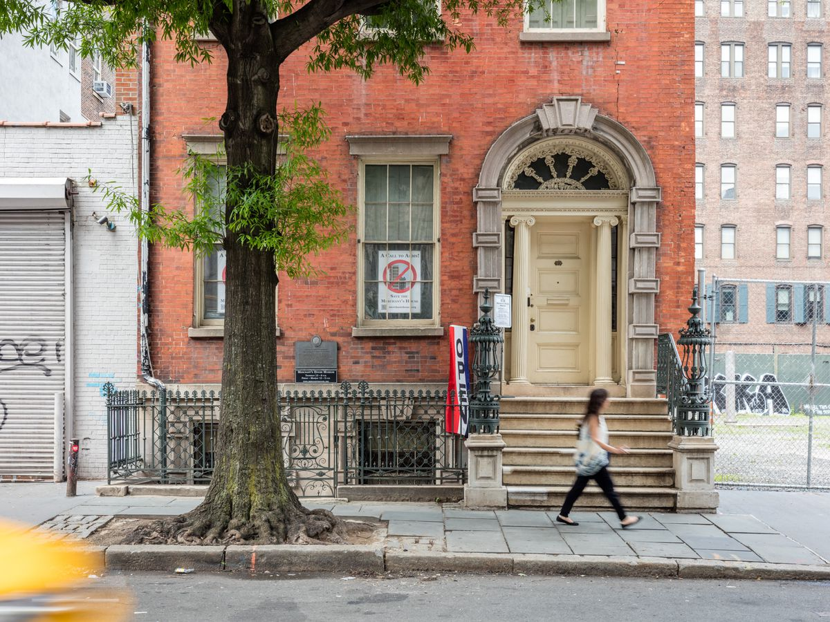 The exterior of the Merchant's House Museum in New York City. The facade is red brick and the door is white with an arched doorframe. There is a tree in front of the building.