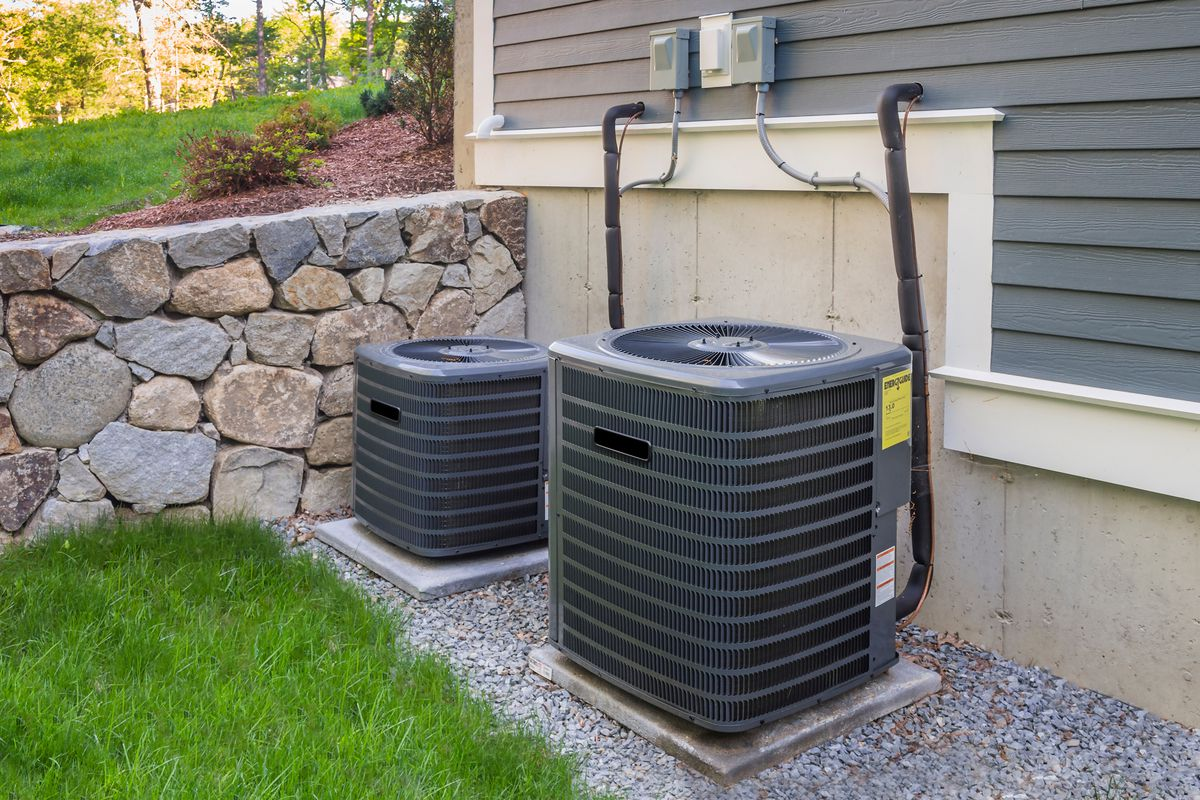 Residential heating and air conditioner compressor units near suburban house.