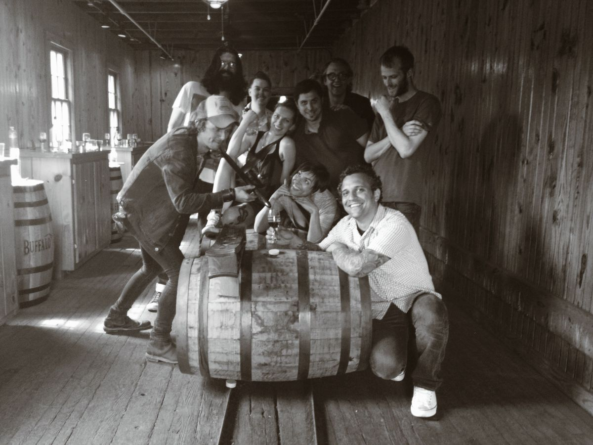 A black-and-white photo of 10 men and women crouching and posing around a bourbon barrel inside a wooden room.