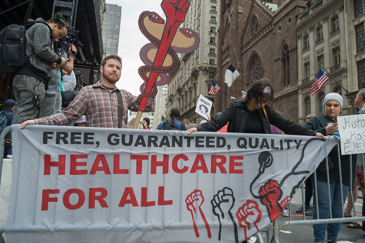 """A protester holds a large cutout caduceus and a banner reading, """"Free, guaranteed, quality healthcare for all."""""""