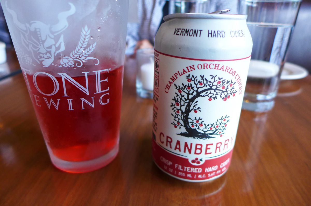 A red glass of cranberry cider with the can on its right.