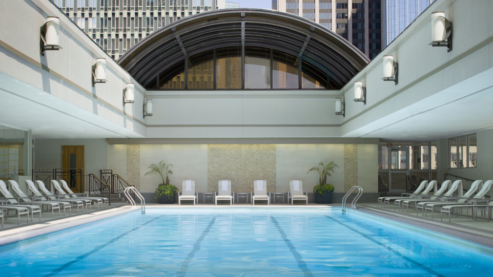 An indoor swimming pool with an open ceiling. There are chairs flanking the pool.