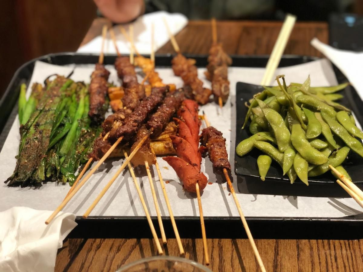 A plate of kabobs and edamame.