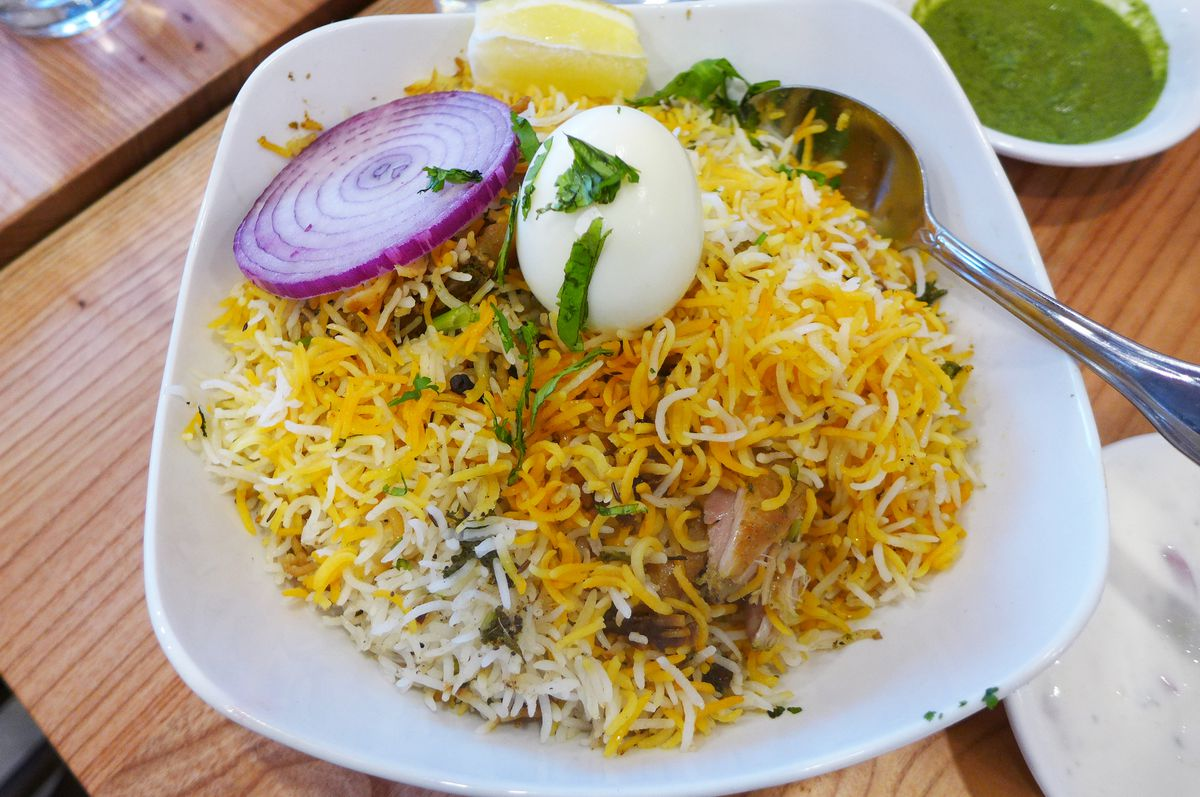 A mountain of yellow rice with a boiled egg and purple onion slice on top.