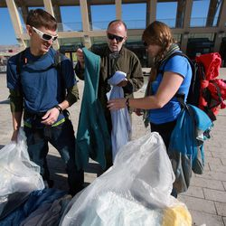 From left, Kevin Langlois, Tom King and Laura England pull out clothes to deliver to people at Pioneer Park while volunteering at the Community Coat Exchange in the Salt Lake City Library Plaza in Salt Lake City on Friday, Nov. 29, 2013.