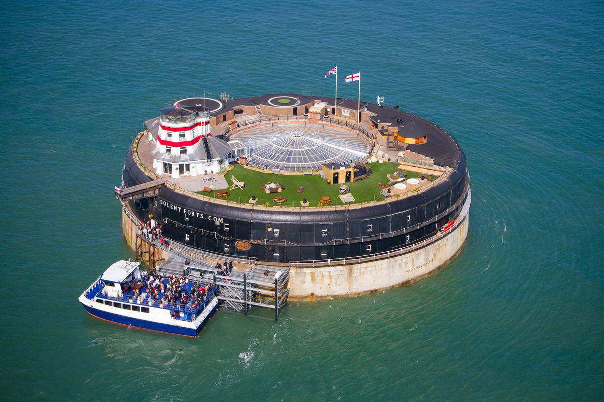 An aerial view of a circular fort in the middle of sea. There is a grass area, lighthouse, flags, and a boat letting off passengers.