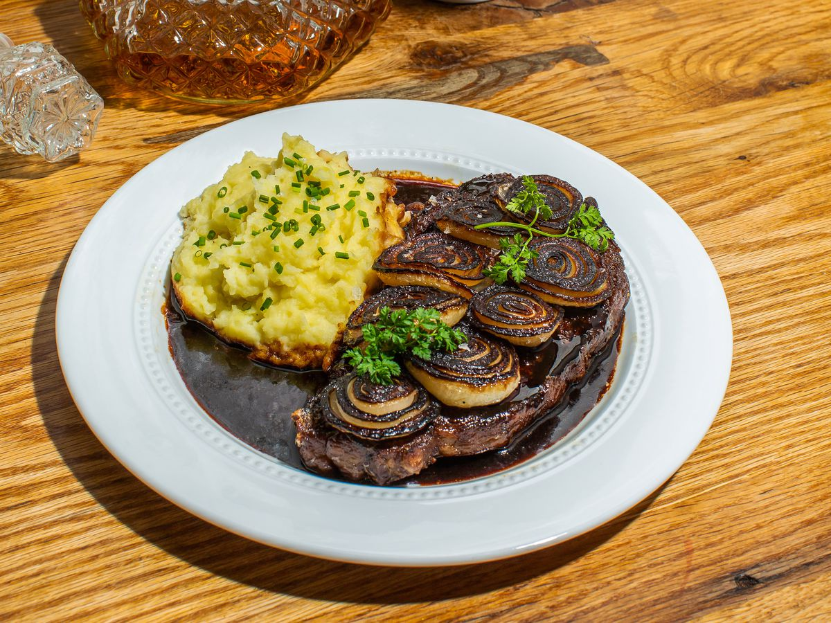 A plate of steak and mashed potatoes, covered in sauce, on a wooden counter beside a pot of flowers