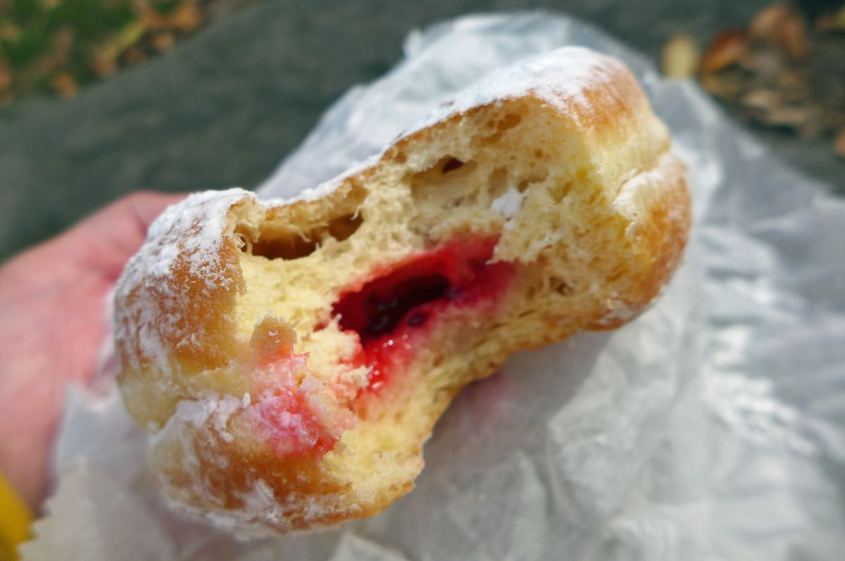 A round doughnut with a bite out of it, red jelly oozing out.