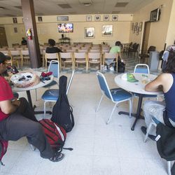 Homeless people seek refuge from the heat and a chance to watch television at the Weigand Homeless Resource Center in Salt Lake City on Thursday, June 29, 2017.